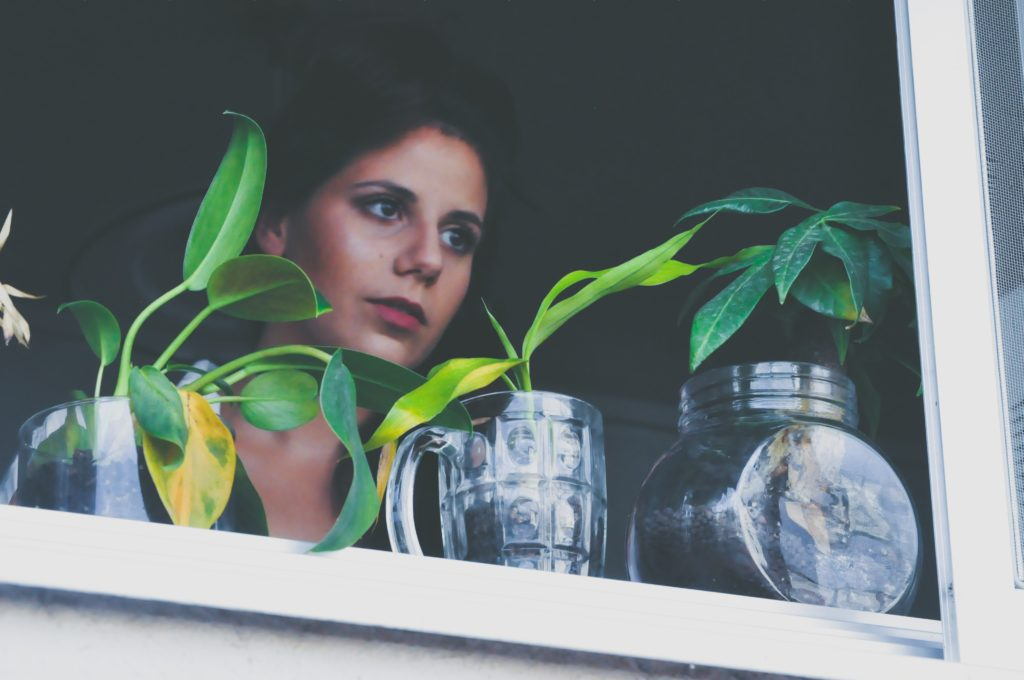 Women looking out a window with small plants on her window sill